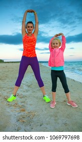 Look Good and feel great. happy healthy mother and daughter in sport style clothes on the seacoast in the evening stretching