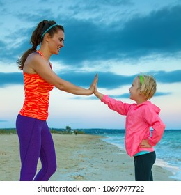 Look Good and feel great. happy young mother in sport style clothes giving child high five on the seacoast in the evening