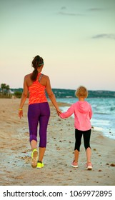 Look Good and feel great. Seen from behind fit mother and child in sport style clothes on the seashore in the evening walking
