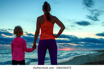 Look Good and feel great. Silhouette. Seen from behind active mother and child in sport style clothes on the seacoast on the sunset looking into the distance