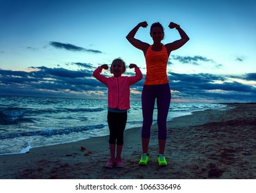 Look Good and feel great. Silhouette. healthy mother and child in sport style clothes on the seacoast on the sunset showing biceps