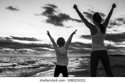 Look Good and feel great. Silhouette. Seen from behind healthy mother and daughter in sport style clothes on the seacoast on the sunset rejoicing