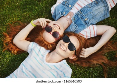 Look of happiness. Two sunny and happy twin sisters with ginger hair lying on green grass and touching heads, playing with hair strands and smiling joyfully, talking about silly things and relaxing