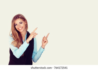 Look here, advertisement. Happy woman smiling showing look here at copy space at my text, product gesture with hands isolated light yellow white background.