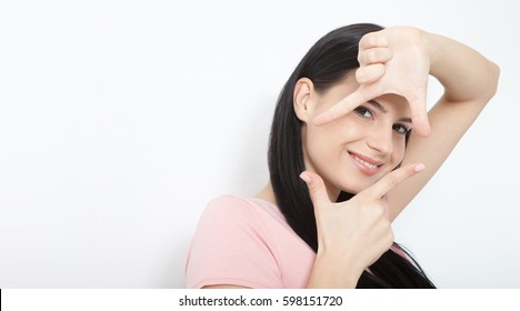 Look here. Attractive young woman showing frame hand and looking at the camera to see the world. Portrait of happy girl your hands up on white background.