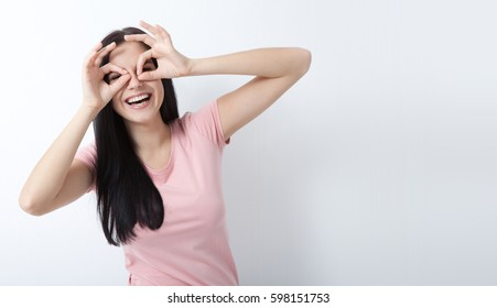 Look here. Attractive young woman looking through binoculars to see the world. Portrait of happy girl your hands up on white background.