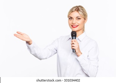 Look here. Cheerful content professional television host holding microphone and smiling ahile doing her job