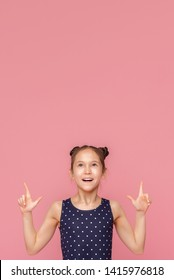 Look here. Cheerful little girl pointing upwards at free space on pink studio background
