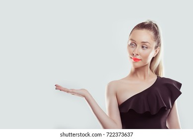 Look here. Closeup portrait happy confident young smiling woman gesturing presenting copy space at right with palm up isolated white wall background. Positive human emotion sign symbol face expression