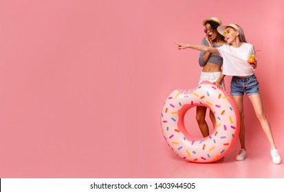 Look here! Emotional female friends in casual wear pointing at empty space, standing with donut inflatable ring on pink studio background