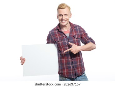 Look here. Handsome smiling man holding white sheet of paper and pointing on it with his index finger against isolated background