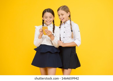 look here. new technology in education. knowledge day. internet surfing with 4g. kids study online. cheerful pupils with smartphone. little girls in school uniform. back to school. educational blog.