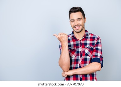 Look here! Young cheerful man with beaming smile is pointing at te copy space with his thumb, wearing casual checkered shirt, standing on light background isolated