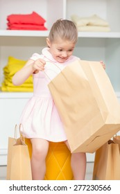 Look inside. Small happy girl looking inside her package with a new dress in a fashion store