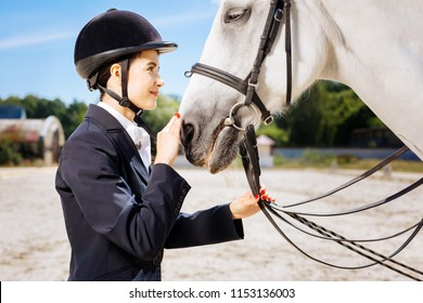 Look into eyes. Appealing dark-haired horsewoman wearing black helmet looking into eyes of her white horse