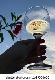 A look into the sky between a bowl of Chardonnay is a hibiscus flower.