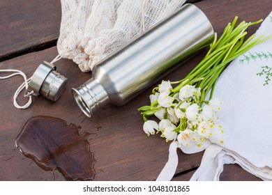 A look into zero waste lifestyle - everyday items. An embroidered textile shopping bag, a produce bag repurposed from old curtains, a durable stainless steel water bottle and a cute bouquet of flowers