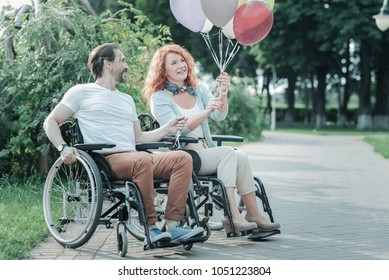 Look at it. Attentive differently abled woman sitting on her wheelchair and expressing positivity while looking at balloons