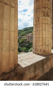 Look at largentiere through the pillars of the neoclassical courthouse in the Ardeche region of France
