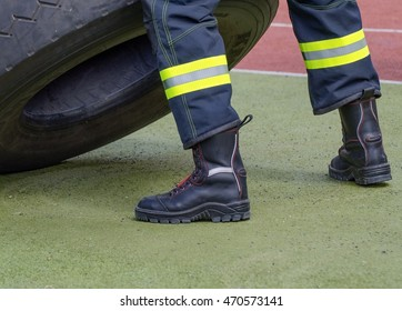 Look at the legs of a fireman in protective boots and pants with reflective tapes.