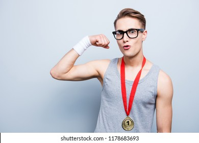 Look at me, I'm the best! Portrait of strong, strength, funny, joke, smart, clever, intelligent youngster man in t-shirt with gold medal show biceps isolated on light gray background