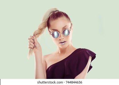 Look at my style, I am all metallic shiny. Woman shows gray metallic mirror lips lipstick in set combination with grey eye glasses, holding blonde dark hair gradient braid isolated on light green