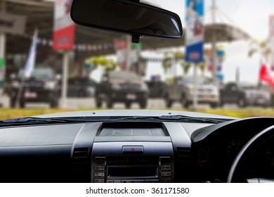 Look out the car window to see blur image of automobile dealers-used cars as background.