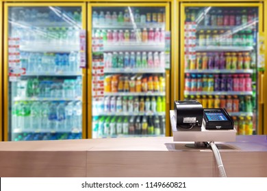 Look out from the payment counter, blur image of beverage cooler inside the convenience store as background.