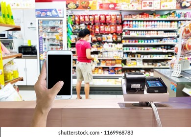 Look out from the payment counter, blur image of women shopping in a convenience store.
