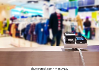 Look out from the payment counter, blur image of clothing store in department store as background.