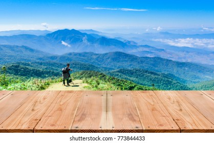 Look out from the table. blur images of tourists are photographed on high mountain scenery as background.