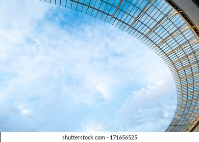 Look over stadium roof with cloudy blue sky