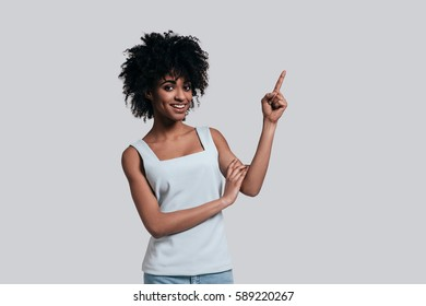 Look over there! Attractive young African woman in casual wear pointing away and smiling while standing against grey background
