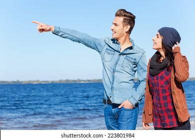 Look over there! Beautiful young couple walking by the beach together while handsome man pointing away and smiling