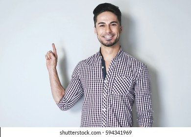 Look over there. Charming and attractive young man in checkered shirt is smiling and gesturing with forefinger to the wall by his right arm against light grey background