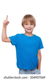 Look over there. Cheerful little boy pointing up and smiling while standing isolated on white