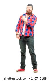 Look over there! Full length of surprised bearded young man in casual wear pointing copy space and smiling while standing isolated on white background