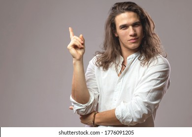 Look over there! Handsome confident man with long hair shows ad. Good looking successful boy in studio. Space for your text or advertisement