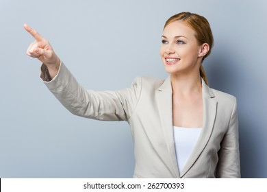 Look over there! Smiling young businesswoman pointing away while standing against grey background