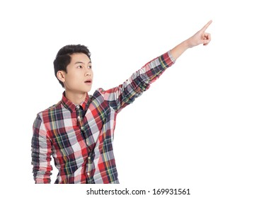 Look over there! Surprised Chinese teenage boy pointing away while standing isolated on white