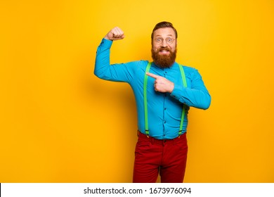 Look. Photo of attractive funny toothy guy raise fist arm indicating finger presenting perfect shape biceps wear blue shirt green suspenders red pants isolated yellow color background