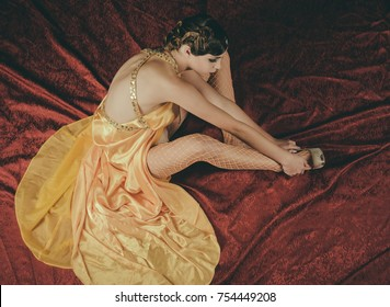 Look and retro style, pinup. Girl in fashionable dress on red blanket in shoes. Woman with stylish retro hair and makeup in stocking. Beauty and vintage fashion. Pin up pretty fashion model.
