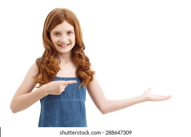 Look and see.  Cute red-haired smiling girl pointing right with two hands and expressing joy while standing isolated on  white background.