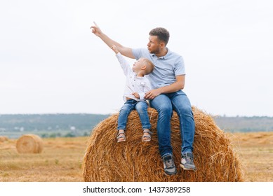 Look at the sky! Father and his son sitting on a haystack or hay roll  in a field pointing to the sky on a plane or something flying.