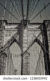 Look up at the suspension cables and arches of a New York City bridge.