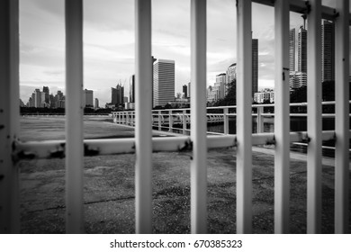 Look at tall buildings in big cities through white steel bars, which depict past black and white memories