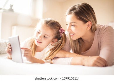 Look that mom. Mother and daughter using digital tablet.