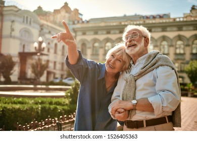 Look at that! Smiling senior woman pointing away and showing something to her husband while spending time together outdoors