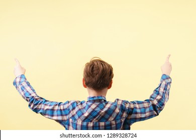look there. approval. cute boy pointing upwards with index fingers over yellow background, back view. advertisement, banner or poster template, emotion facial expression, people reaction