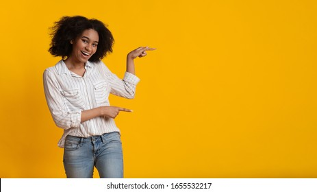 Look There. Happy Black Woman Pointing Fingers Aside At Copy Space Over Yellow Background, Advertising Something, Panorama